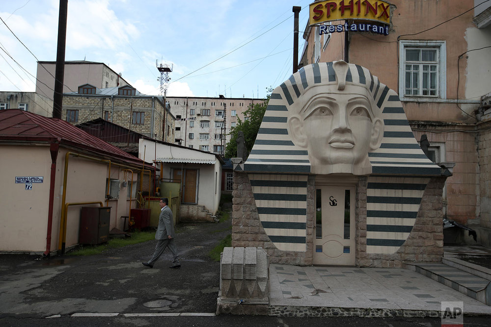 In this Thursday, May 10, 2018, a pedestrian passes outside a restaurant in Stepanakert.  (AP Photo/Thanassis Stavrakis)