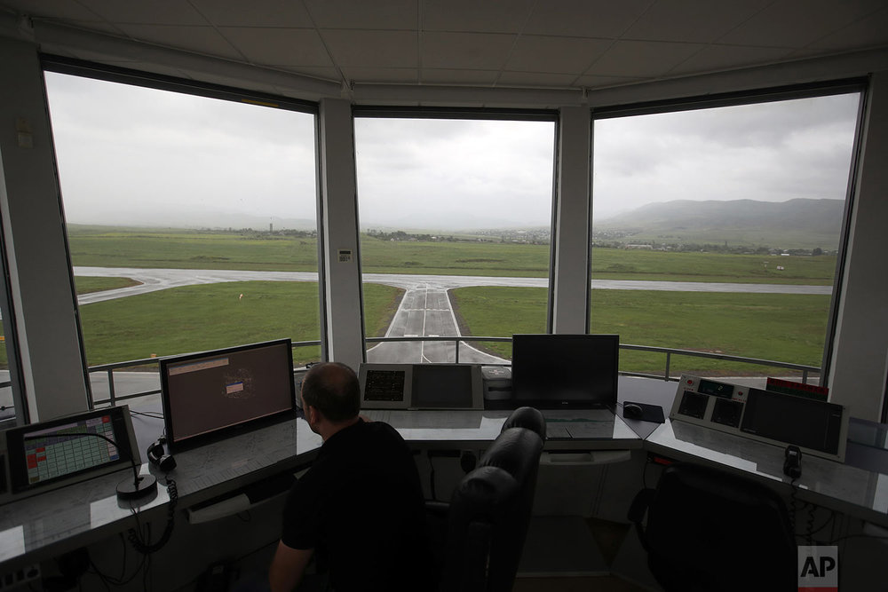 In this Friday, May 11, 2018, a man watches a screen atop the air-traffic control tower at the empty Stepanakert airport. (AP Photo/Thanassis Stavrakis)