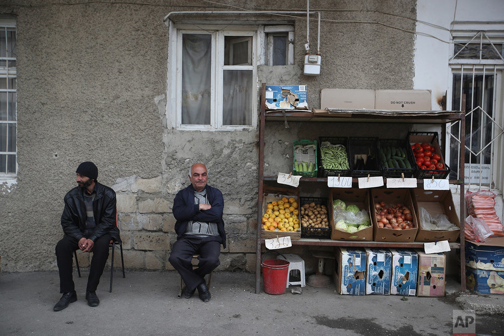 In this Tursday, May 10, 2018, a fruit vendor with his friend sit outside his shop in Stepanakert. AP Photo/Thanassis Stavrakis)