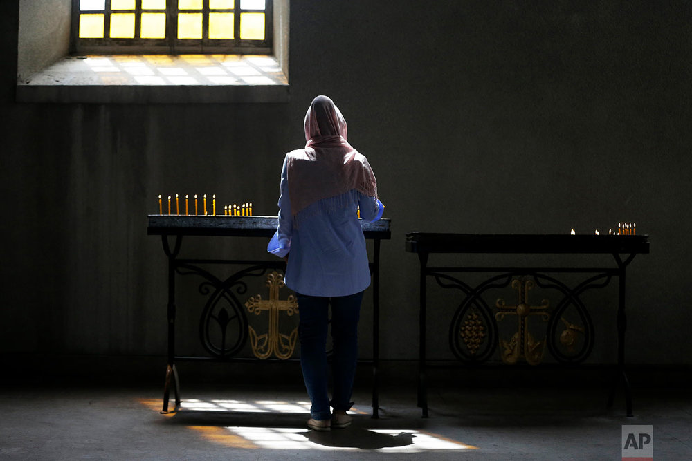 In this Thursday, May 10, 2018, a woman lights a candle at a church in Shusha town.  (AP Photo/Thanassis Stavrakis)