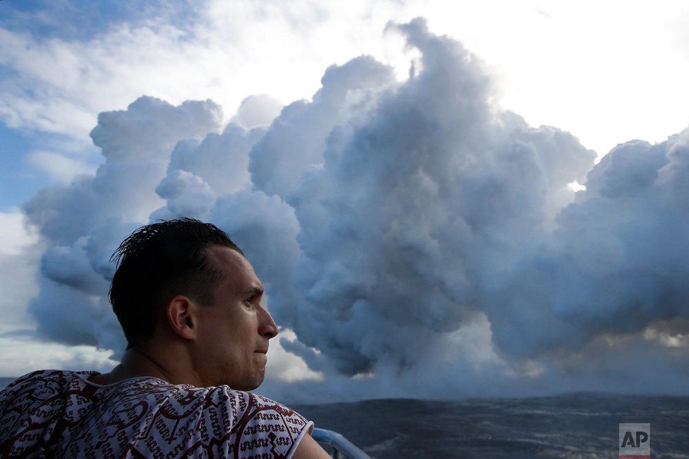 Gabor Kovacs, visiting from Hungary, watches as lava flows into the ocean, generating plumes of steam, near Pahoa, Hawaii,  May 20, 2018. (AP Photo/Jae C. Hong)