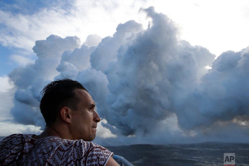 Gabor Kovacs, visiting from Hungary, watches as lava flows into the ocean, generating plumes of steam, near Pahoa, Hawaii, May 20, 2018. (AP Photo/Jae C. Hong)