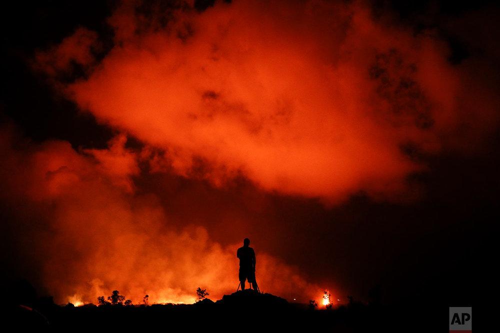 Peter Vance, 24, photographs lava erupting in the Leilani Estates subdivision near Pahoa, Hawaii, May 18, 2018. (AP Photo/Jae C. Hong)