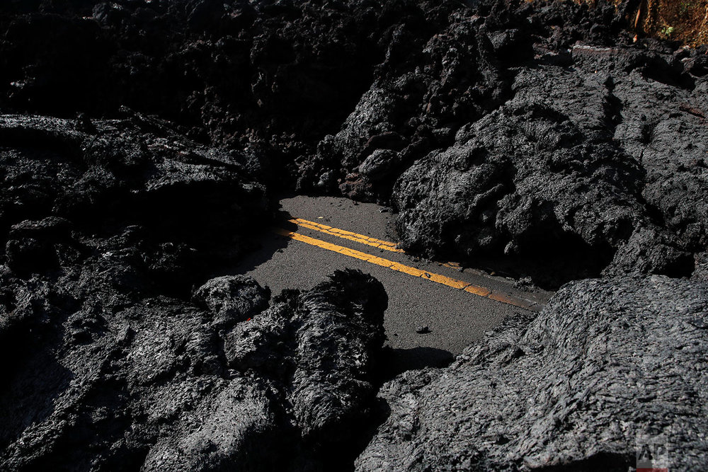 Center lane lines are partially visible along the lava-covered road in the Leilani Estates subdivision near Pahoa, Hawaii, May 11, 2018.  (AP Photo/Jae C. Hong)