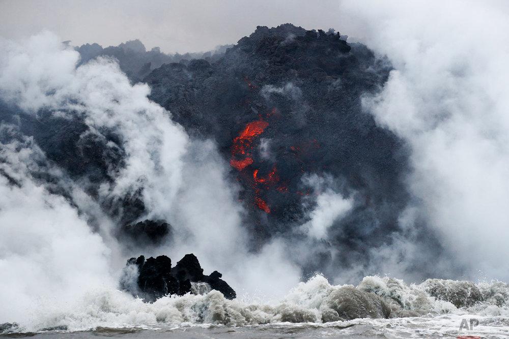 Lava flows into the ocean near Pahoa, Hawaii, May 20, 2018. (AP Photo/Jae C. Hong)