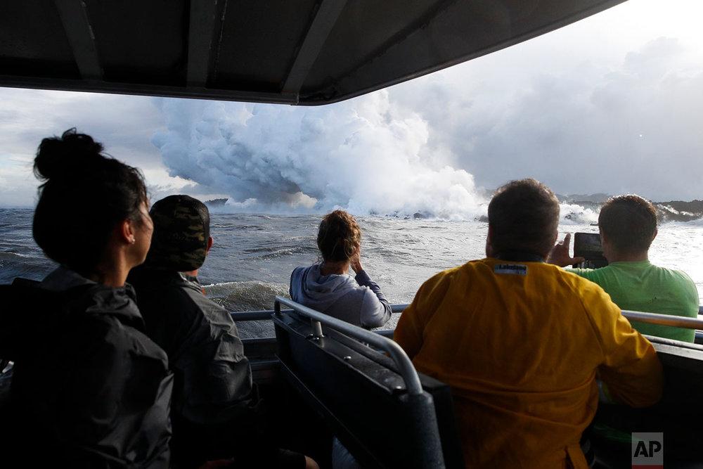 People watch a plume of steam as lava enters the ocean near Pahoa, Hawaii, May 20, 2018. (AP Photo/Jae C. Hong)