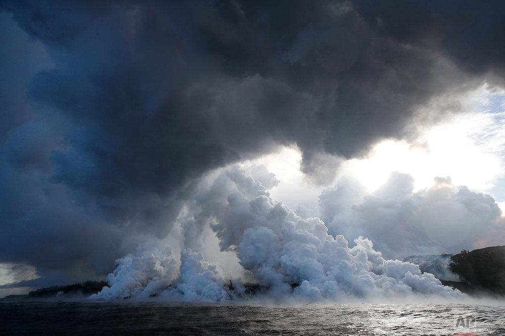 Plumes of steam rise as lava enters the ocean near Pahoa, Hawaii, May 20, 2018. (AP Photo/Jae C. Hong)