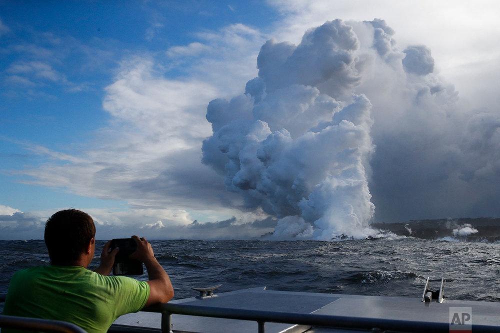 Joe Kekedi takes pictures as lava enters the ocean, generating plumes of steam near Pahoa, Hawaii, May 20, 2018. (AP Photo/Jae C. Hong)