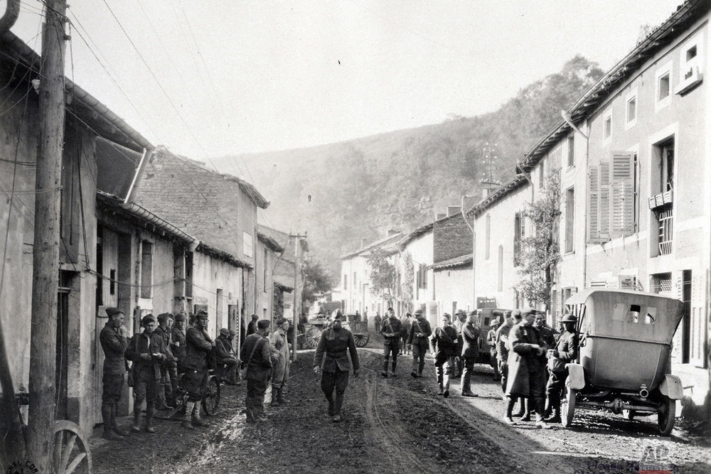 This photo provided by National World War I Museum and Memorial and dated Sept. 20, 1918, shows American soldiers in Bouillonville, eastern France, and the hill in the background which protects the village from German shells. Bouillonville was the center of the medical unit for a large part of the German Army. Many medical supplies were found and our medical units were using the German hospitals the same day the drive started. (National World War I Museum and Memorial via AP)