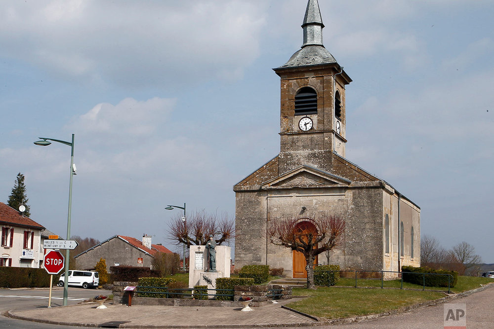 This photo dated March 25, 2018, shows the church in Beauclair, Meuse region, eastern France. The WWI memorial, center left, stands in front of the church. (AP Photo/Laurent Rebours)