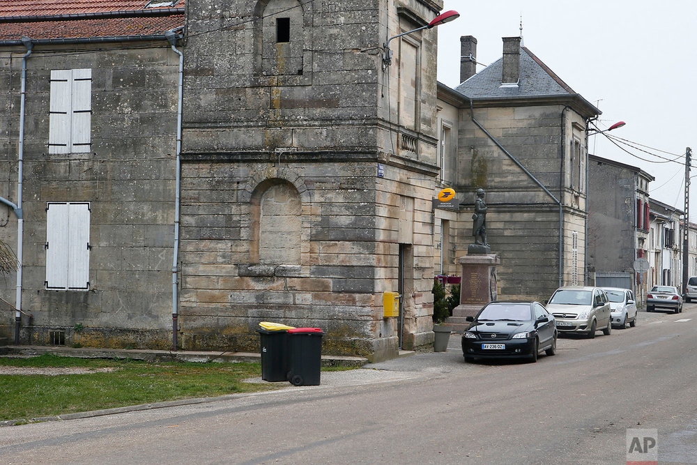 This photo dated March 26, 2018, shows the former school in Conde-en-Barrois, Meuse region, eastern France. A WWI memorial stands in front of the school, center right. (AP Photo/Laurent Rebours)