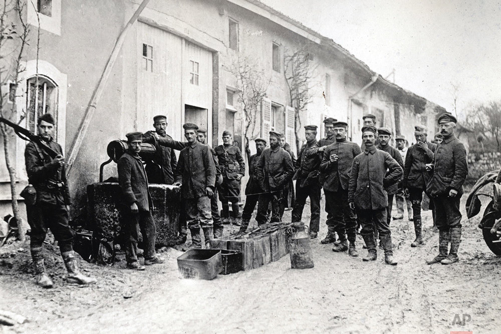 This photo provided by National World War I Museum and Memorial and dated Nov. 9, 1918 shows an American soldier, left, guarding German prisoners captured in Battle of Argonne by 35th Div., drawing water from a well for their mess, in Pierrefitte-sur-Aire, eastern France. (National World War I Museum and Memorial via AP)