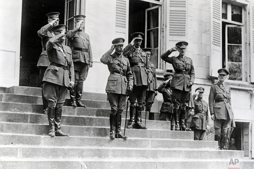 In this photo provided by National World War I Museum and Memorial and dated Aug. 6, 1918, Britain's King George V, center left 1st row, visits the 33rd Div. and distributes honor medals in Molliens-au-Bois, northern France. The official party stand at salute as the national anthems are played. Left to right : Gen. John J. Pershing, Gen. Tasker H. Bliss, Maj. Gen. George Bell, Jung George, Gen. Holman and Maj. Gen. Hamilton. (National World War I Museum and Memorial via AP)
