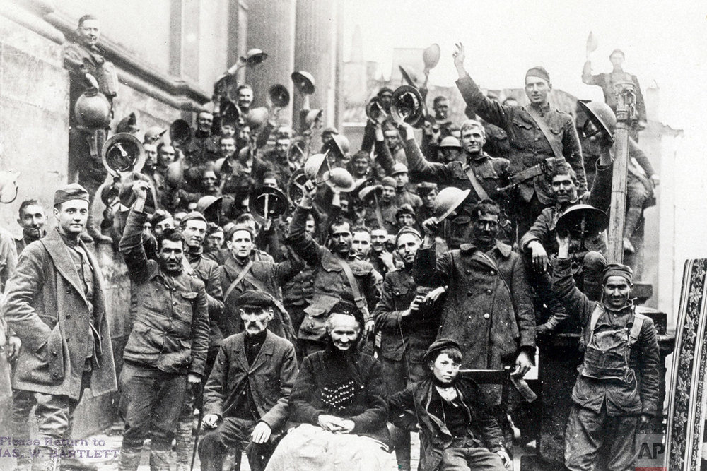 This photo provided by National World War I Museum and Memorial and dated Nov. 11, 1918 shows celebrations or armistice by Company A, 353rd Regiment Infantry, 89th Div., at church steps which they reached at 11:00am, in Stenay, Meuse region, eastern France. (National World War I Museum and Memorial via AP)