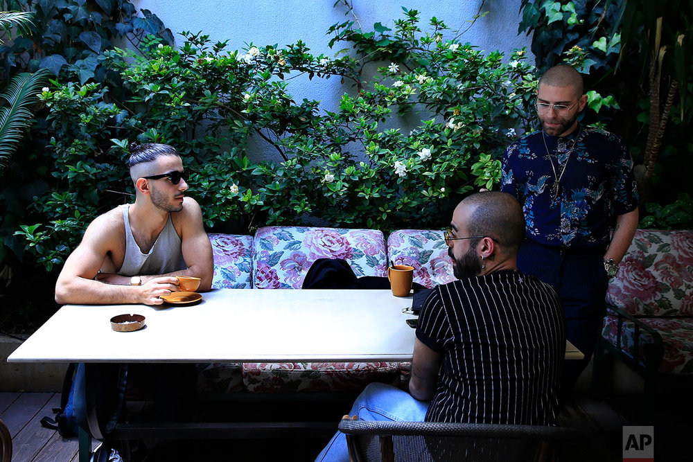 In this picture taken Saturday, May 12, 2018, Elias, 24, right who goes by the stage name of Melanie Coxxx drinks coffee with his friends at a restaurant during the launch event of Beirut Pride week in Beirut, Lebanon.  (AP Photo/Hassan Ammar)