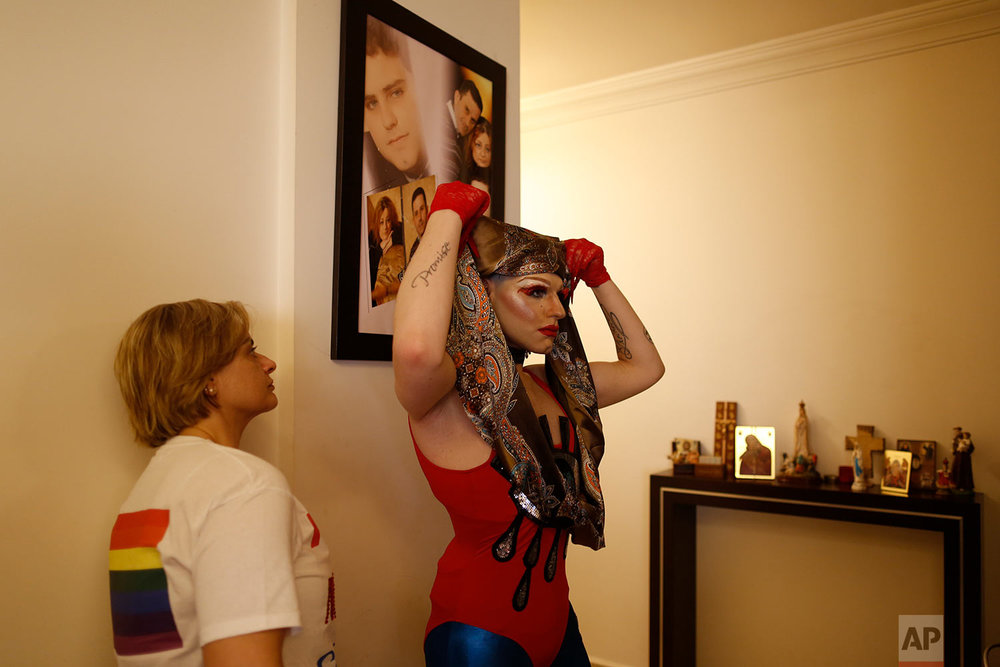 In this picture taken Sunday, May 13, 2018, Valerie, left, looks to her son Elias, 24, who goes by the stage name of Melanie Coxxx, fixes his scarf before performing in a Sunday drag show, called the drag ball, during Beirut Pride week at his home in Tabarja, Lebanon. (AP Photo/Hassan Ammar)
