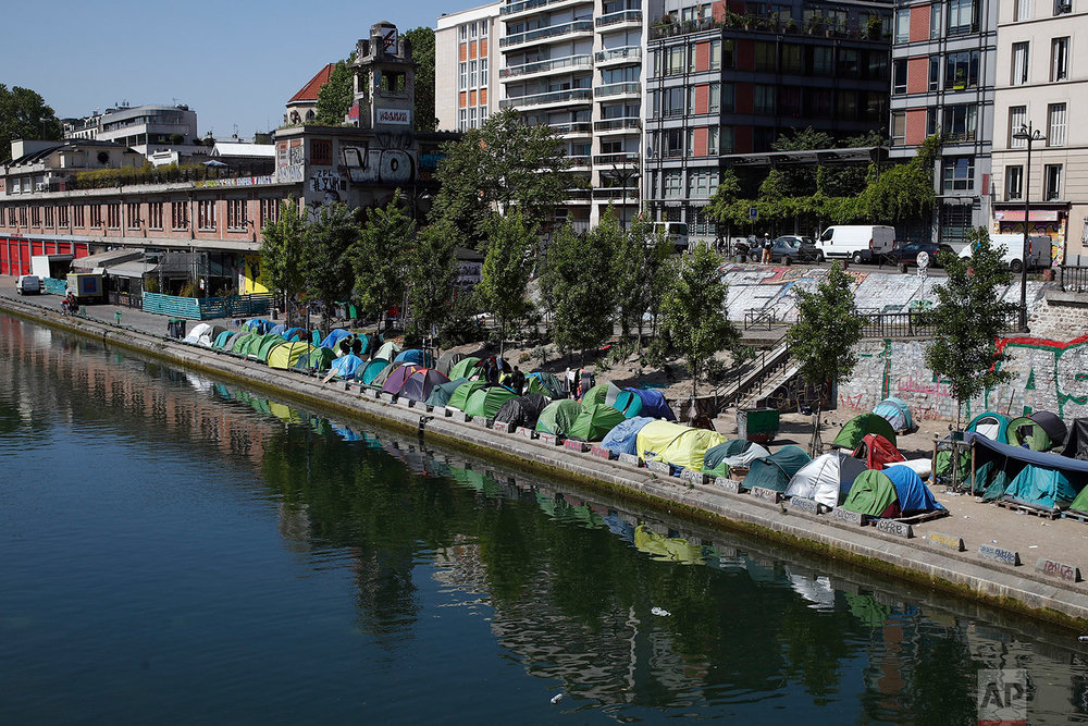 Tents where asylum seekers have set up a makeshift camp line the edge of the Canal Saint-Martin, in Paris, Friday, May 18, 2018. (AP Photo/Francois Mori)
