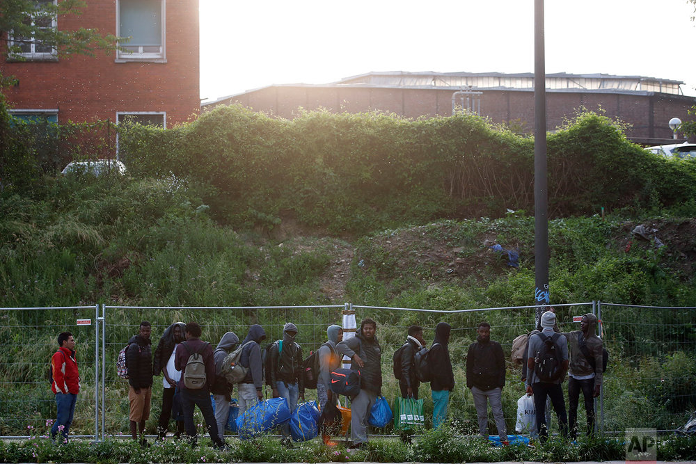 Migrants line up in a makeshift camp during its evacuation, in Paris, Wednesday, May 30, 2018. (AP Photo/Thibault Camus)
