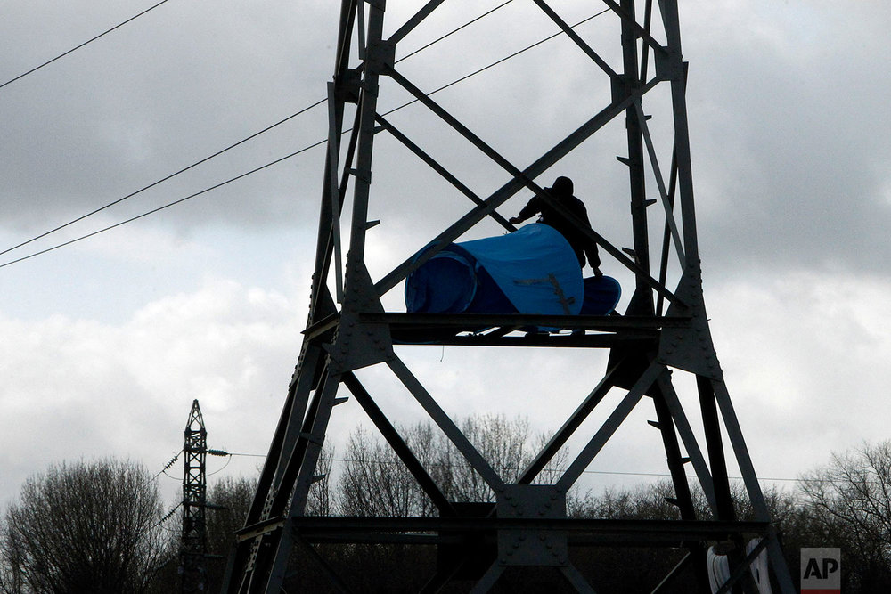 A man sets up a tent in an electric pole in Calais, northern France, Feb. 2, 2018. (AP Photo/Michel Spingler)