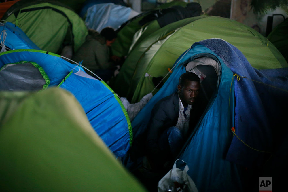 A migrant is shown in his tent during the evacuation of a makeshift camp, in Paris, Wednesday, May 30, 2018. (AP Photo/Thibault Camus)