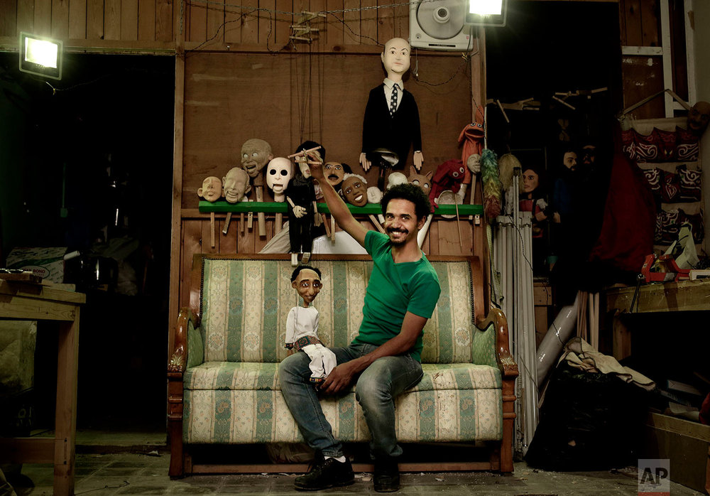 Egyptian artist Mohamed Fawzi Bakkar poses for a photograph with his favorite puppets at his workshop, in Cairo, Egypt, April 24, 2018. (AP Photo/Nariman El-Mofty)