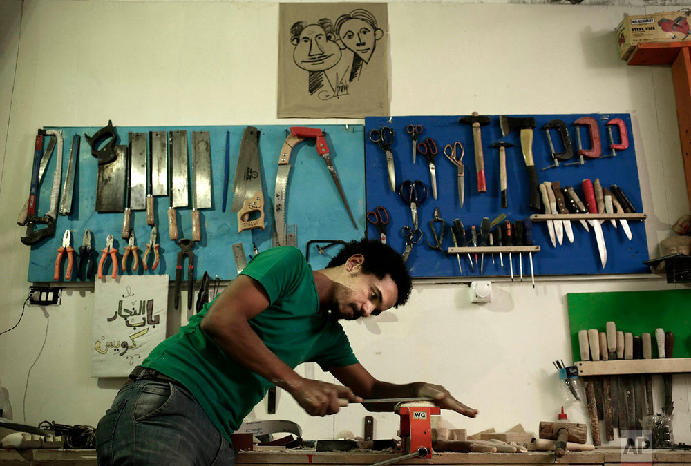 Egyptian artist Mohamed Fawzi Bakkar works on a puppet with wood at his workshop, in Cairo, Egypt, In this April 24, 2018 photo, . (AP Photo/Nariman El-Mofty)