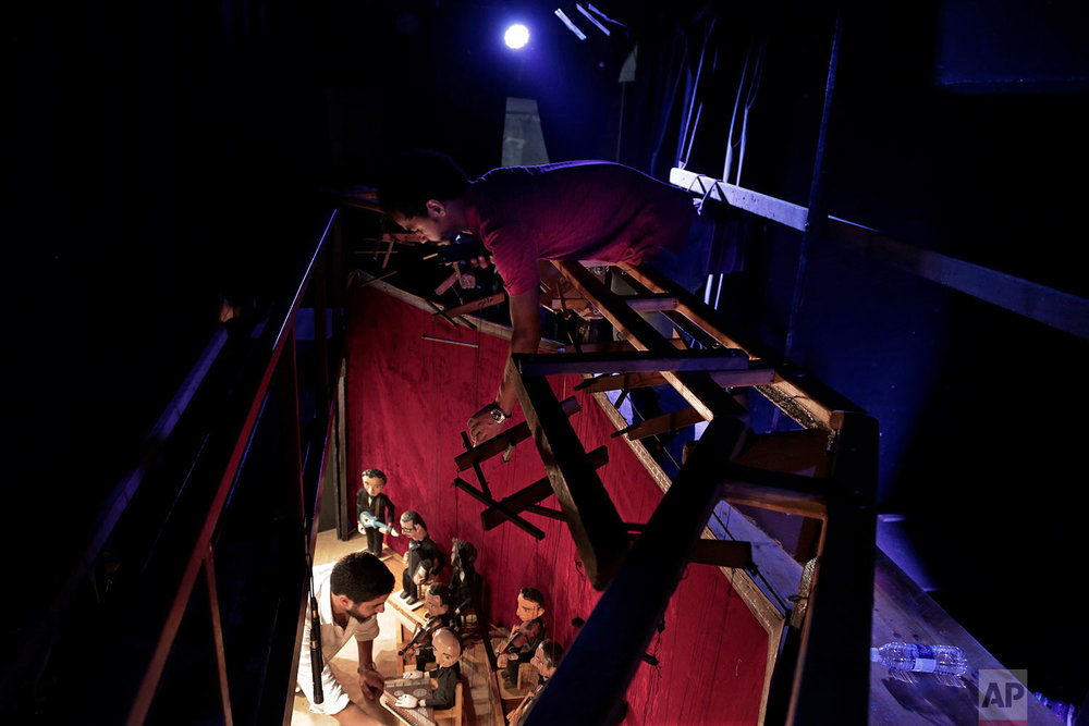 Egyptian marionette artist Mohamed Fawzi Bakkar, top, prepares puppets during a performance at the El Sawy Cultural Center, in Cairo, Egypt, May 3, 2018. (AP Photo/Nariman El-Mofty)