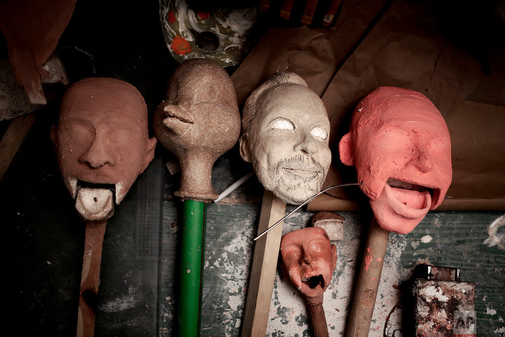 Sculptures of puppet faces made by Egyptian artist Mohamed Fawzi Bakkar, lay on a table at his workshop, in Cairo, Egypt, April 24, 2018.(AP Photo/Nariman El-Mofty)