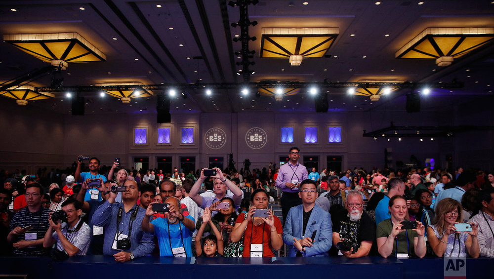 Parents and supporters gather in front of the stage to photograph the medal winners advancing to the final round of the Scripps National Spelling Bee in Oxon Hill, Md., Wednesday, May 30, 2018. (AP Photo/Carolyn Kaster)