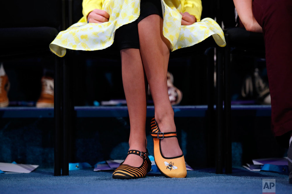 Simone Kaplan, 12, from Davie, Fla., wears shoes with bee themes on them during the 2nd Round of the Scripps National Spelling Bee, Tuesday, May 29, 2018, in Oxon Hill, Md. (AP Photo/Alex Brandon)