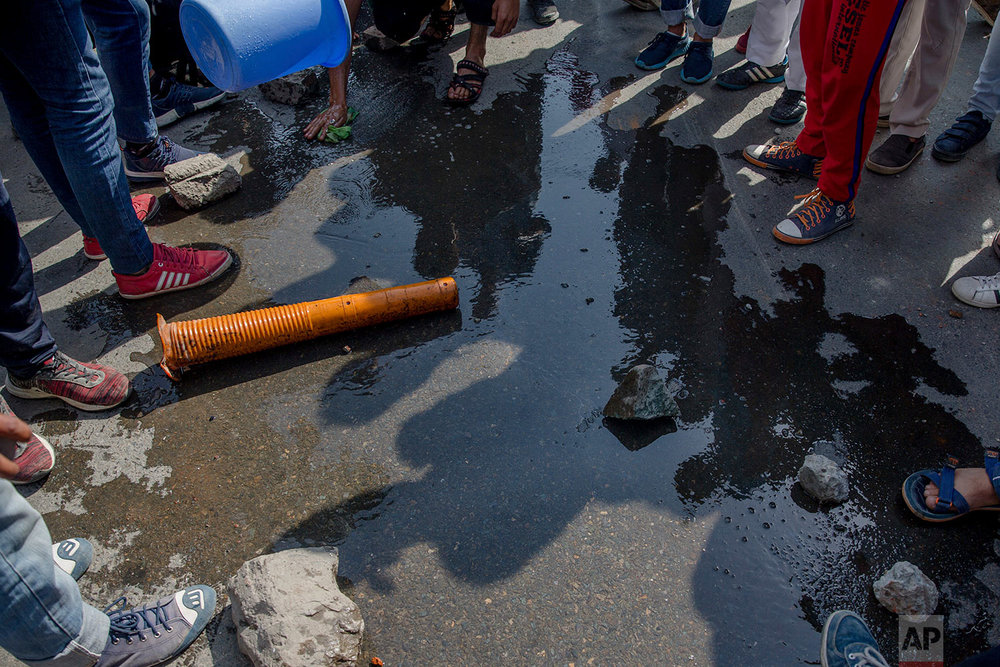 Kashmiri men wash the blood stained road after a paramilitary vehicle ran over a man during a protest in Srinagar, Indian controlled Kashmir, Friday, June 1, 2018. (AP Photo/Dar Yasin)