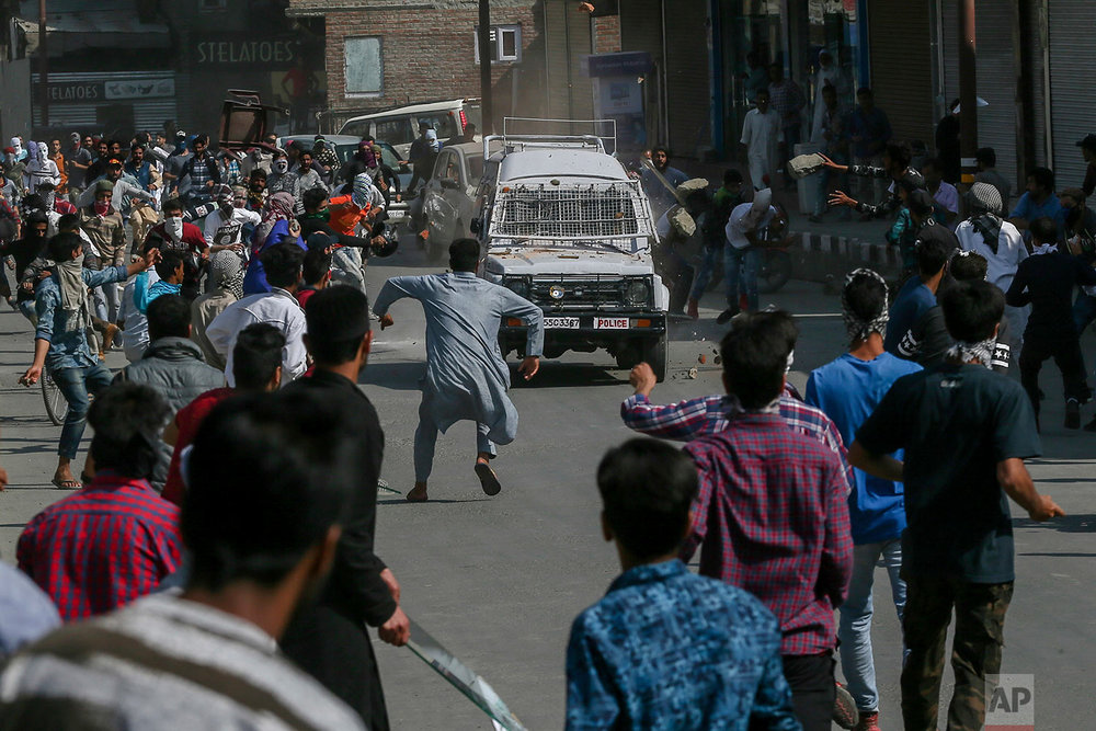 Kashmiri Protesters throw rocks and bricks on a paramilitary vehicle in Srinagar, Indian controlled Kashmir, Friday, June 1, 2018. (AP Photo/Dar Yasin)