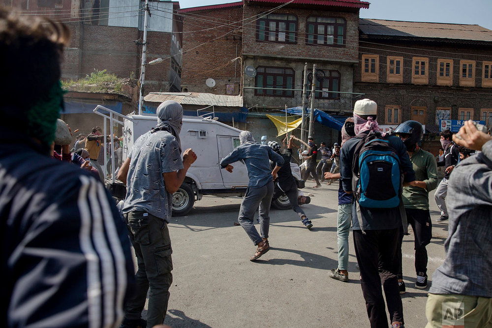 Kashmiri Protesters gather around an Indian paramilitary vehicle as it runs over a man during a protest in Srinagar, Indian controlled Kashmir, Friday, June 1, 2018. (AP Photo/Dar Yasin)