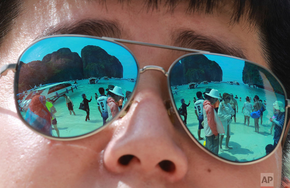 In this Thursday, May 31, 2018, photo tourists are reflected in sunglasses on Maya Bay on Phi Phi island in Krabi province, Thailand. Maya Bay on Phi Phi Leh Island in the Andaman Sea will close to tourists for four months from Friday to give its coral reefs and sea life a chance to recover from an onslaught that began nearly two decades ago. (AP Photo/Sakchai Lalit)