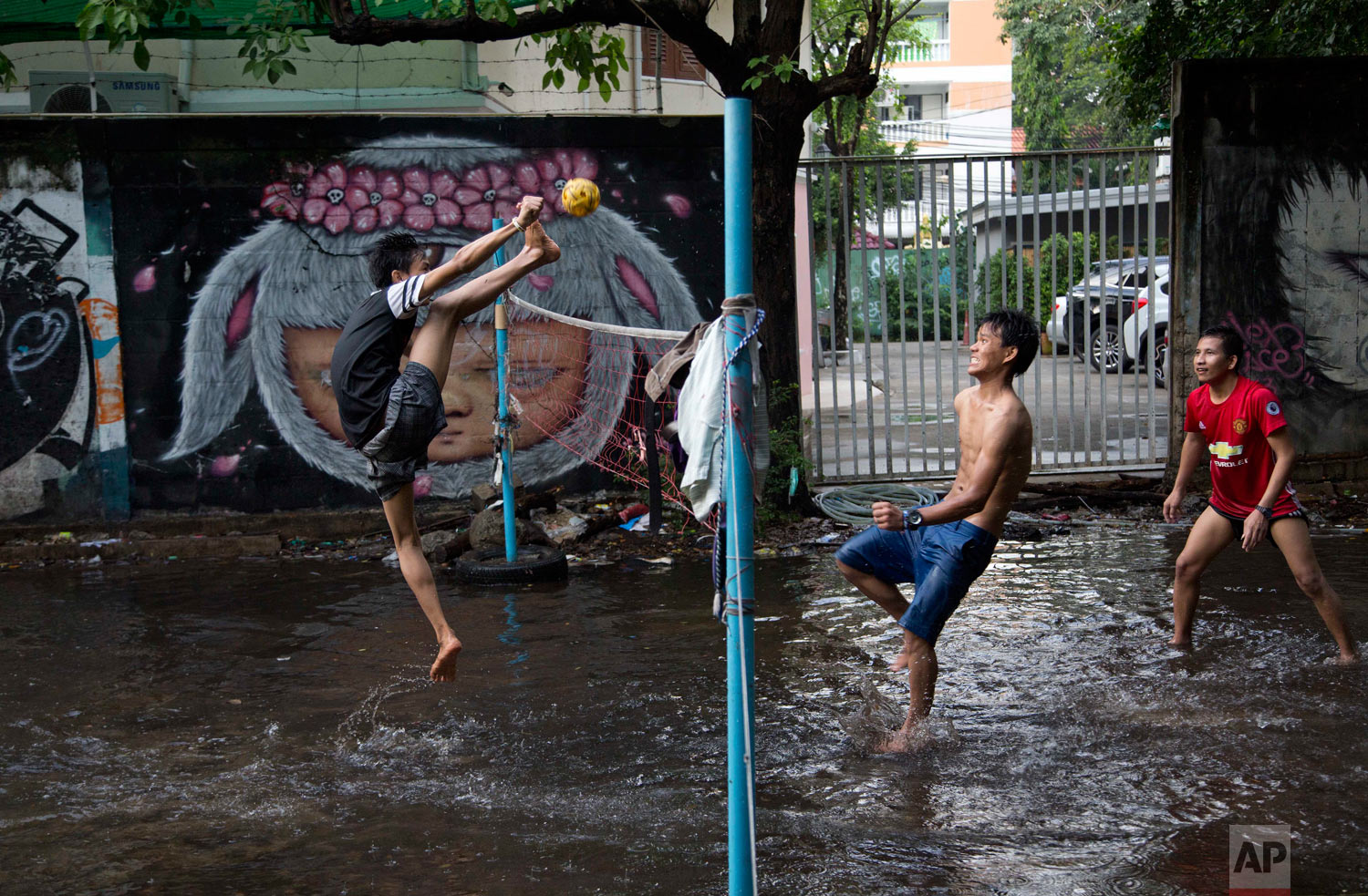 An airborne migrant worker kicks a rattan ball during a game of Chinlone in a field flooded by rain water in Bangkok, Thailand, Thursday, May 31, 2018. The popular Burmese sport Chinlone, a combination of sport and dance, is played between two teams consisting of six players each, passing a rattan ball back and forth with feet, knees and heads. (AP Photo/Gemunu Amarasinghe)