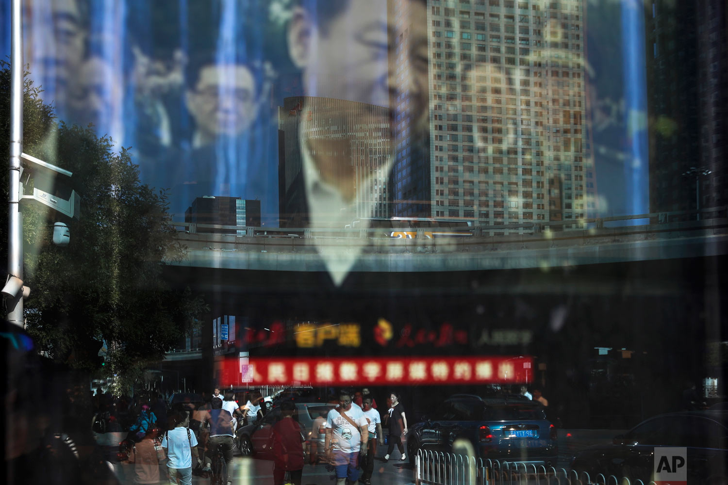 In this Wednesday, May 30, 2018, photo, people and motorists in morning rush hour are reflected on an electronic display panel advertising a video footage of Chinese President Xi Jinping near the Central Business District in Beijing. Chinese factory activity grew at its fastest rate in eight months on stronger demand, a survey showed Thursday, May 31, 2018 in a positive sign for the world's No. 2 economy despite trade tensions with the U.S. China's services industry is playing a bigger role as communist leaders upgrade economic growth, shifting it from a worn-out model based on wasteful trade and investment to one focused on domestic spending. (AP Photo/Andy Wong)
