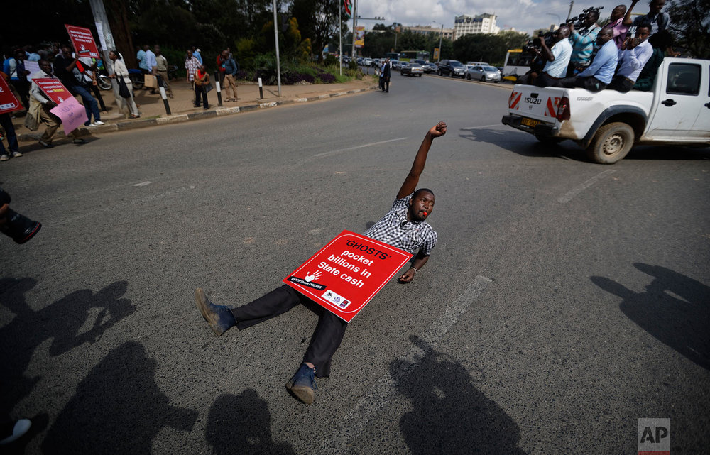 A protester lies down on the street during an anti-corruption demonstration by hundreds of protesters who marched to the Parliament and Supreme Court in downtown Nairobi, Kenya, Thursday, May 31, 2018. Kenya's leader is under increasing pressure as outrage grows over a number of corruption scandals involving tens of millions of dollars revealed in recent weeks around the ministries of health, energy, agriculture, public service and youth. (AP Photo/Ben Curtis)