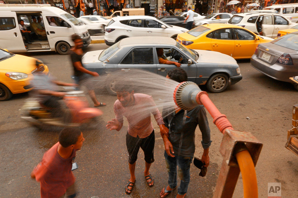People cool off from the summer heat under an open air shower in Baghdad, Iraq, Wednesday, May 30, 2018. The temperature in Baghdad reached 109 F (42 C) on Wednesday. (AP Photo/Hadi Mizban)