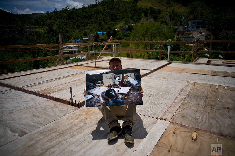 Luis Cosme poses as he holds a printed photo taken on Oct. 1, 2017, after Hurricane Maria,  in the San Lorenzo neighborhood of Morovis, Puerto Rico, May 26, 2018. (AP Photo/Ramon Espinosa)