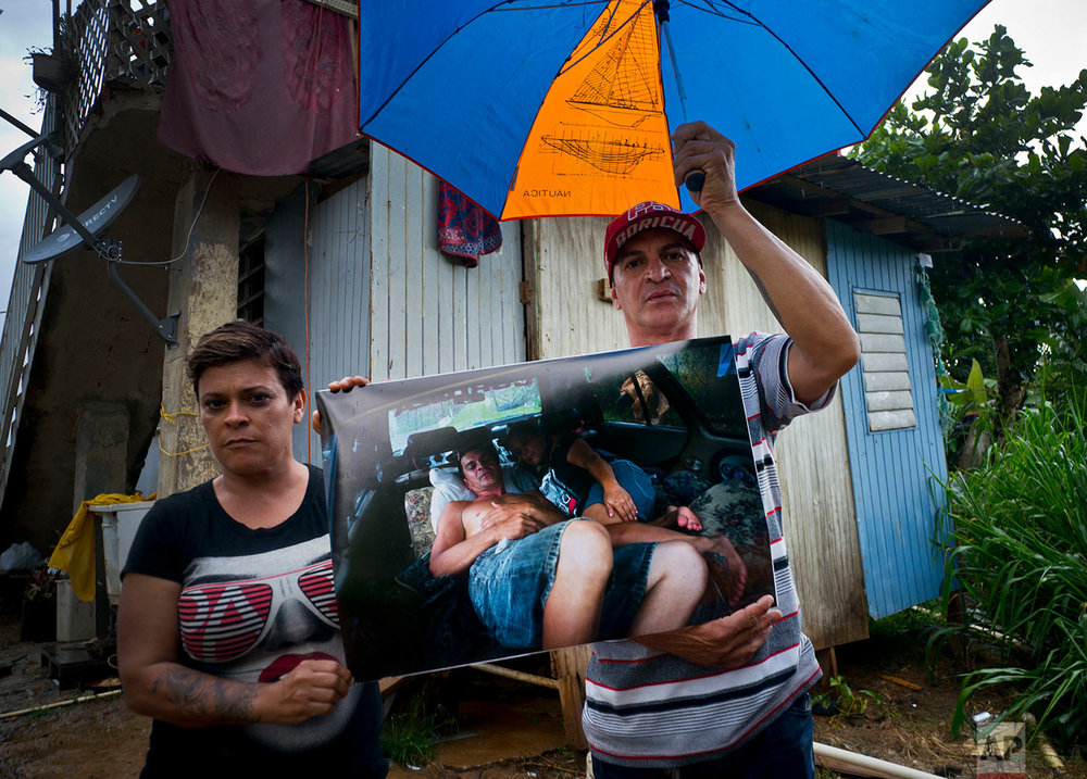 Blanca Rivera and Eduard Rodriguez pose with a printed photo on Sept. 30, 2017 as they slept in their car after their home was destroyed by Hurricane Maria in the San Lorenzo neighborhood of Morovis, Puerto Rico, May 26, 2018. (AP Photo/Ramon Espinosa)