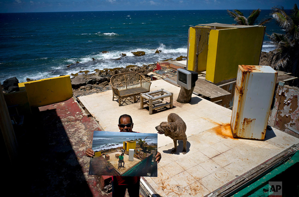 Roberto Figueroa Caballero holds a printed photo taken on Oct. 5, 2017 of him amid his seaside home that was destroyed by Hurricane Maria, in the La Perla neighborhood of San Juan, Puerto Rico, May 29, 2018. (AP Photo/Ramon Espinosa)
