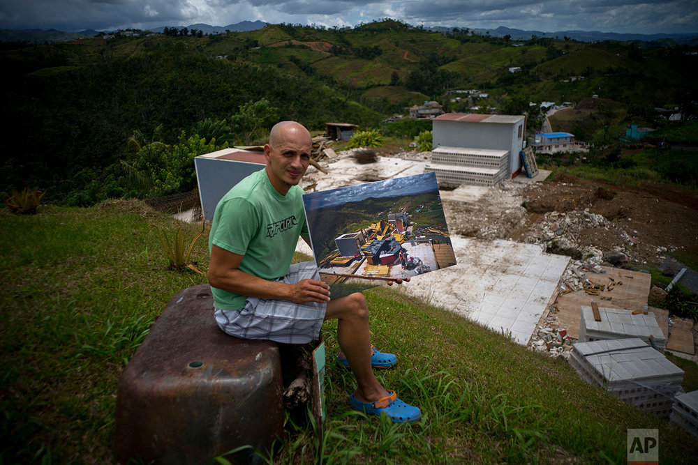 Rafael Reyes holds a printed photo of him taken on Oct. 7, 2017 after his home was destroyed by Hurricane Maria, in the San Lorenzo neighborhood of Morovis, Puerto Rico, May 26, 2018. (AP Photo/Ramon Espinosa)