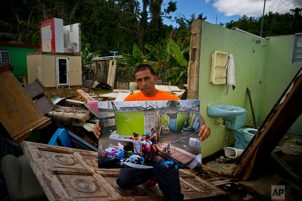 Arden Dragoni holds a printed photo taken on Oct. 5, 2017 that shows him with his family, after his home that was destroyed by Hurricane Maria, in Toa Baja, Puerto Rico, May 28, 2018. (AP Photo/Ramon Espinosa)