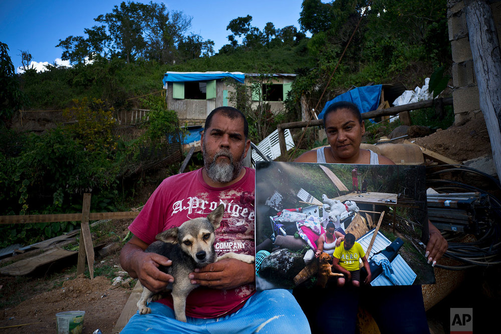 William Fontan Quintero and his wife Yadira Sostre pose with a printed photo of them taken on Sept. 30, 2017 after Hurricane Maria, in the San Lorenzo neighborhood of Morovis, Puerto Rico, May 29, 2018. (AP Photo/Ramon Espinosa)