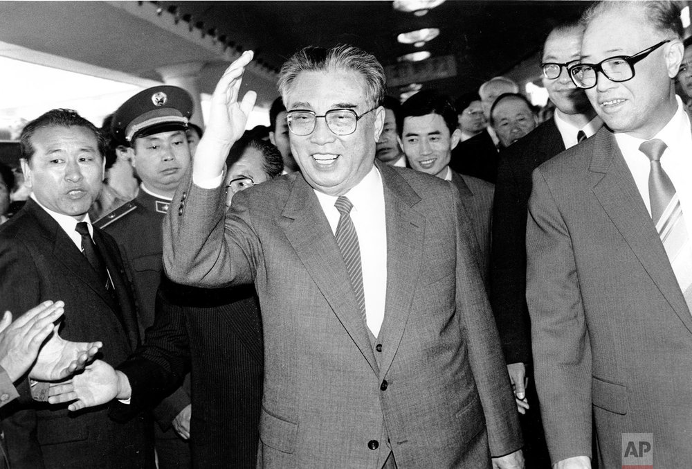 North Korean President Kim Il Sung, center, and Chinese Premier Zhao Ziyang make their way through a crowd of well-wishers at the train station in Beijing on May 21, 1987. (AP Photo/Neal Ulevich)