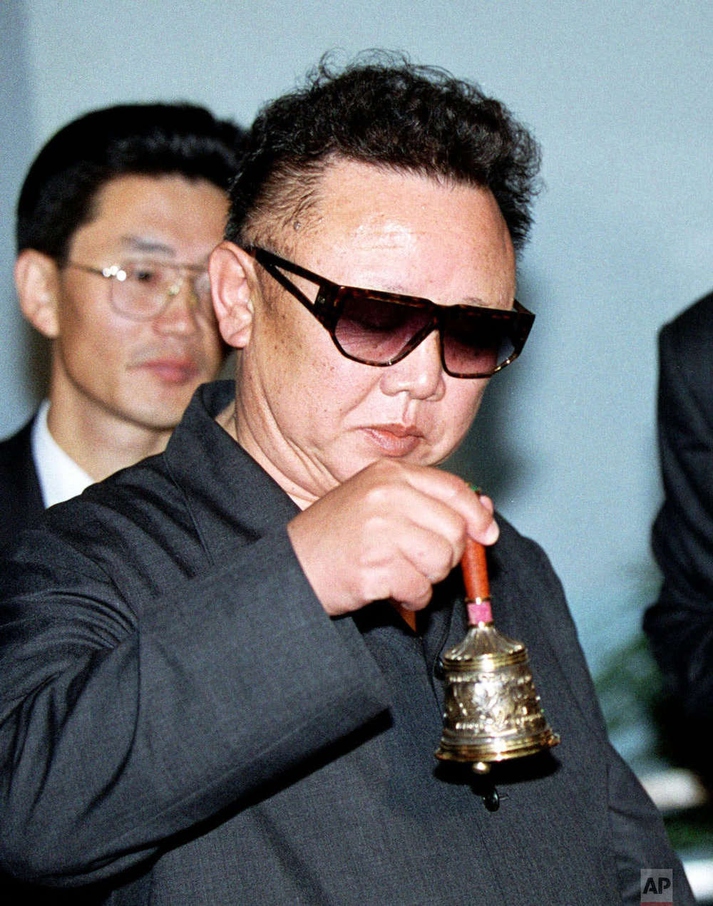 North Korea's leader Kim Jong Il rings a bell that was presented to him at the railway station in Khasan, Russia, just over the border from North Korea, on July 26, 2001, at the start of a 10-day train journey to Moscow on the Trans-Siberian Railway. This was Kim's third foreign trip as leader of his impoverished and isolated country. (AP Photo/Igor Kochetkov)