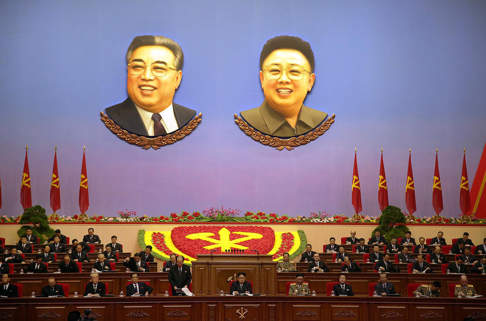 Portraits of late North Korean leaders Kim Il Sung, left, and his son, Kim Jong Il, hang inside the convention hall of the April 25 House of Culture, where the party congress is held in Pyongyang, North Korea, on May 9, 2016. Kim Jong Un, just named party chairman, sits at center. (AP Photo/Wong Maye-E)