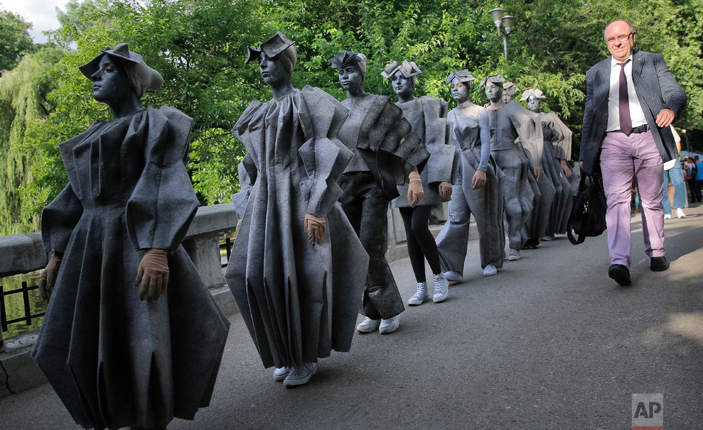 Artists of Romania's Masca theatre wear outfits inspired by famous Romanian sculptor Constantin Brancusi's iconic Endless Column, at the Living Statues International Festival, in Bucharest, Romania on Thursday, May 24, 2018. (AP Photo/Vadim Ghirda)