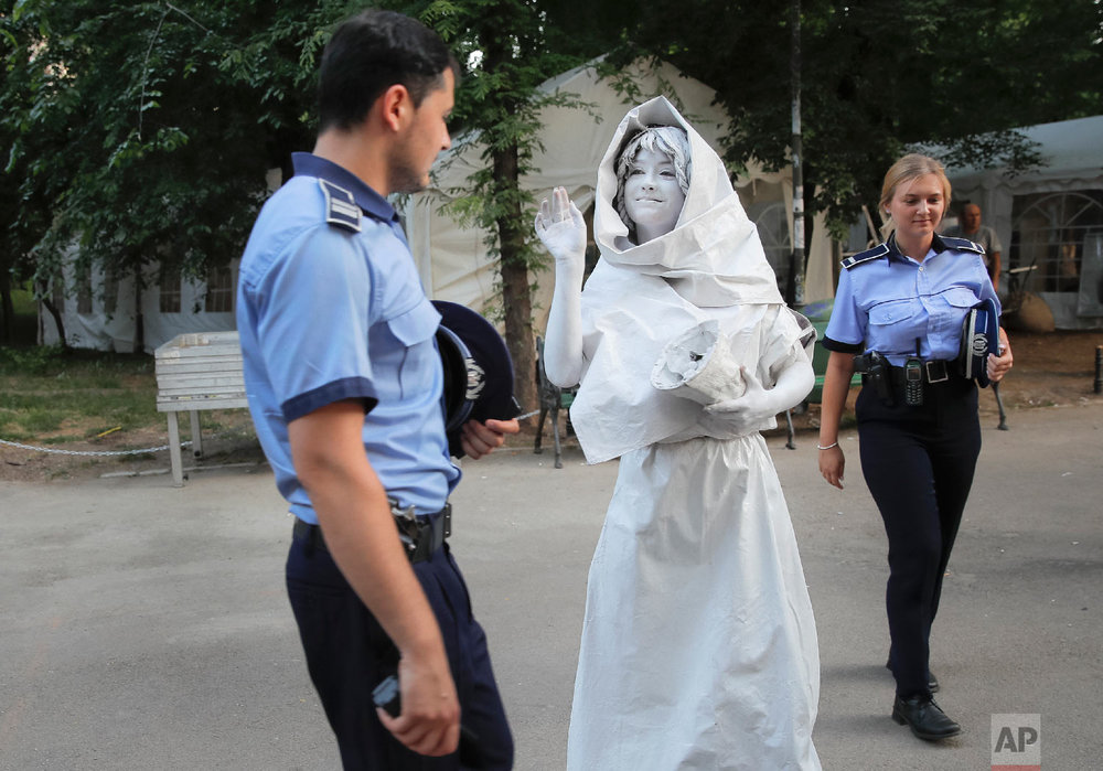 An artist of Ukraine's Artel Myth, walks by Romanian police officers, in Bucharest, May 24, 2018. (AP Photo/Vadim Ghirda)