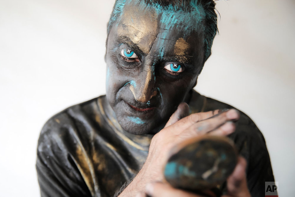 Portuguese artist Antonio Santos checks his make-up during the Living Statues International Festival, in Bucharest, Romania on Sunday, May 27, 2018. (AP Photo/Vadim Ghirda)